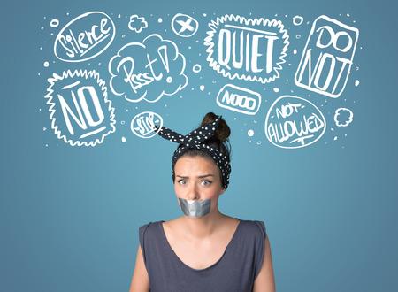 boca cerrada: Mujer joven con la boca pegada y blancas dibujadas nubes de pensamiento alrededor de la cabeza