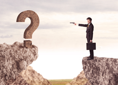 bridging: Businessman standing on the edge of mountain with a rock question mark on the other side Stock Photo