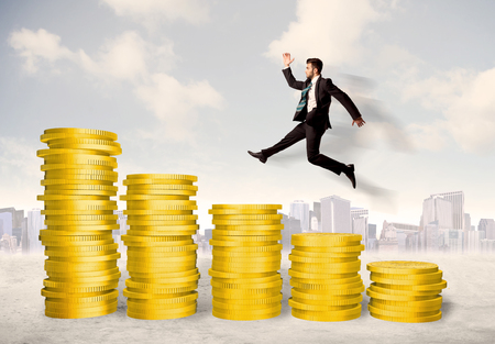 growing business: Successful business man jumping up on gold coin money concept Stock Photo