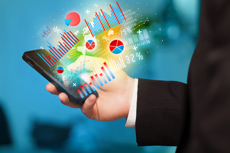 web application: Business man holding smartphone with chart symbols concept Stock Photo