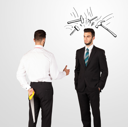 holding gun to head: Ruthless businessman hiding a weapon white drawn beating hammer marks Stock Photo
