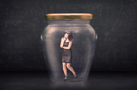 imprisoned: Businesswoman shut inside a glass jar concept concept on background