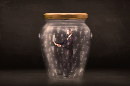 trapped: Business man trapped in jar with exclamation marks concept on bakcground