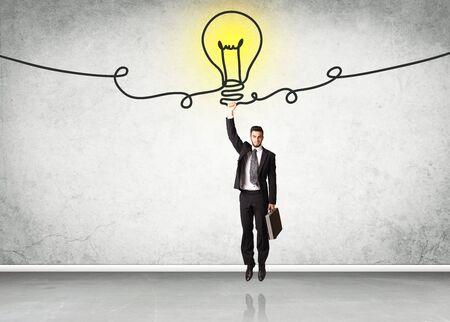Businessman hanging on an idea bulb
