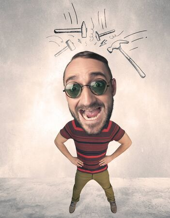big head: Funny person with big head and drawn punching hammers over it Stock Photo