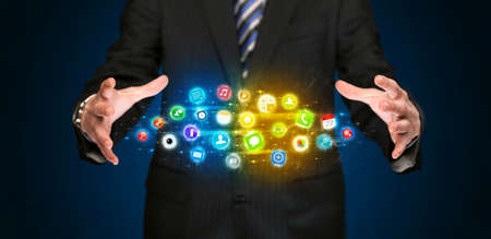 virtual technology: Businessman holding a shining app icon cloud in front of his body Stock Photo