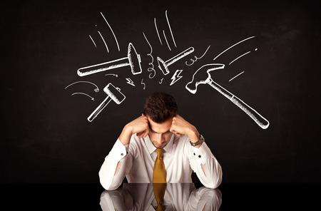 depresión: Joven hombre de negocios deprimido sentado bajo blancas dibujadas marcas de golpes de martillo Foto de archivo