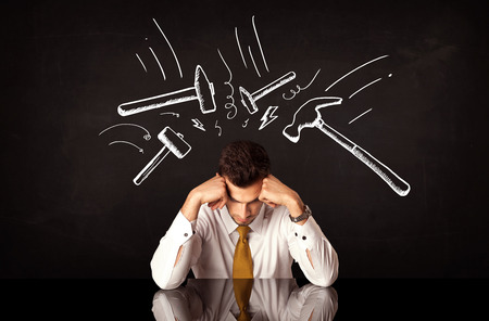 depression: Young depressed businessman sitting under white drawn beating hammer marks Stock Photo