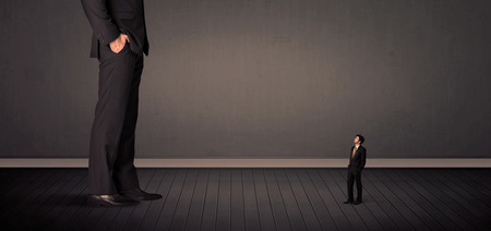 bussinesman: Little bussinesman in front of a giant boss legs concept on background