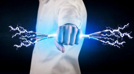 electrical networks: Persona de negocios que sostiene el�ctrica concepto cables con alimentaci�n en el fondo