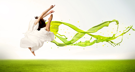 flying woman: Pretty girl jumping with green abstract liquid dress concept in nature Stock Photo