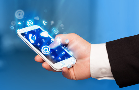 internet icon: Business man holding smart phone with media icons concept on background Stock Photo