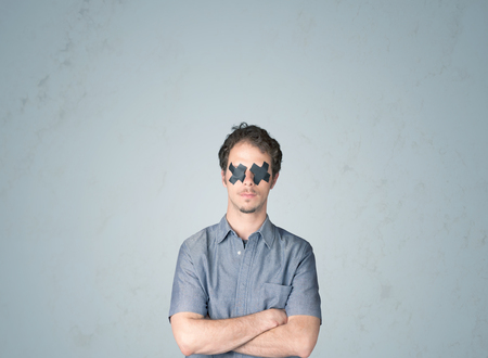 sellotape: Young man with taped eye. Isolated on gray background