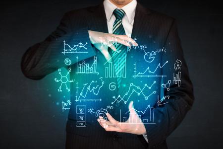 schemes: Businessman holding hand drawn business schemes Stock Photo