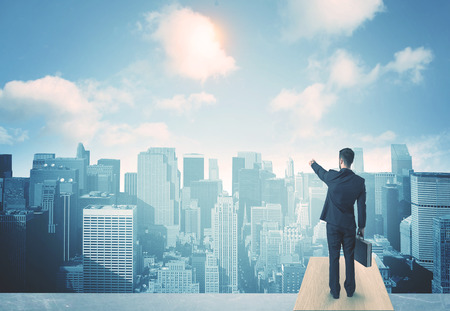 confidence: Businessman standing on a roof and looking at future city Stock Photo