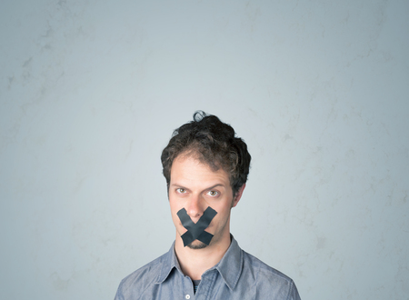 dismay: Young man with taped mouth. Isolated on gray background