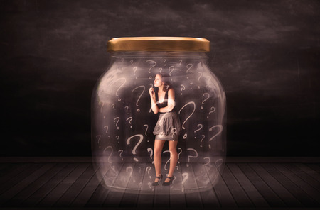locked up: Businesswoman locked into a jar with question marks concept on background Stock Photo