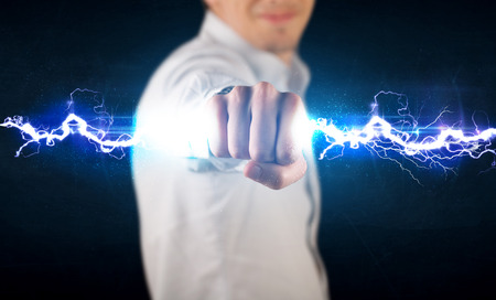 electrical power: Business man holding electricity light bolt in his hands concept