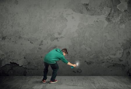graffiti: Pintor urbano joven que comienza a dibujar graffiti en la pared