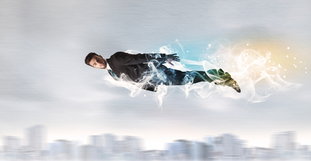 left behind: Hero superman flying above city with smoke left behind concept Stock Photo
