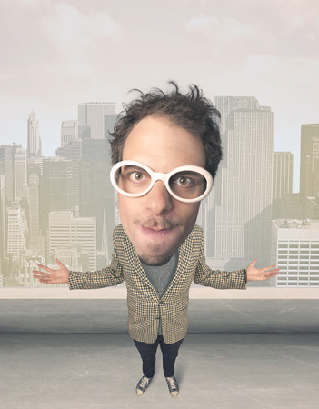 exaggeration: Funny guy with big head, cityscape background Stock Photo