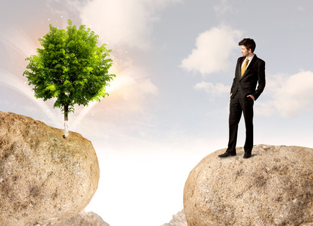 other side of: Businessman standing on the edge of rock mountain with a tree on the other side Stock Photo