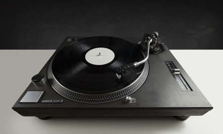 audiophile: Turntable playing vinyl close up with needle on the record with grey background Stock Photo