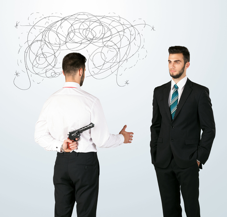 hidden danger: Ruthless businessman hiding a weapon and weaving plan around his head Stock Photo