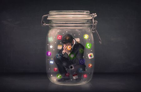 network connections: Businessman captured in a glass jar with colourful app icons concept on background