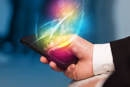 holding smart phone: Hand holding smart phone with abstract glowing lines concept