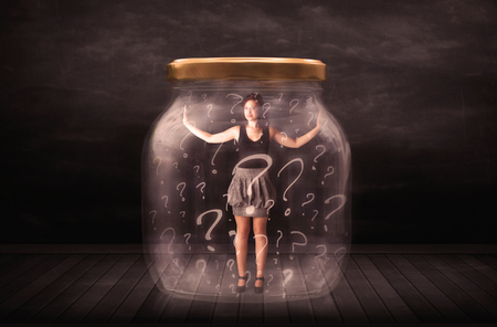 Businesswoman locked into a jar with question marks concept on background Stock Photo