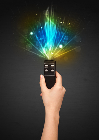 out of control: Hand holding a remote control, shining and explosive signal coming out of it