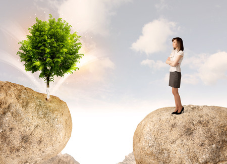 bridging the gap: Businesswoman standing on the edge of rock mountain with a tree on the other side
