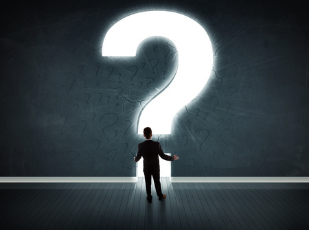punto di domanda: Uomo d'affari guardando il muro con un concetto di punto interrogativo luminoso