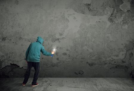 artistas: Pintor urbano joven que comienza a dibujar graffiti en la pared