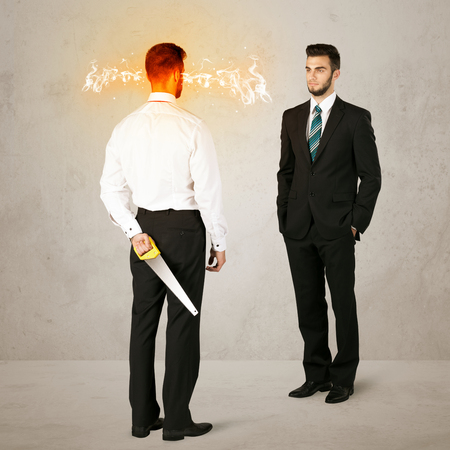 hidden danger: Angry businessman hiding a weapon behind his back Stock Photo