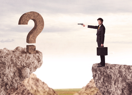 bridging the gaps: Businessman standing on the edge of mountain with a rock question mark on the other side Stock Photo