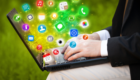 comming: Hand pressing modern laptop with mobile app icons and symbols comming out Stock Photo