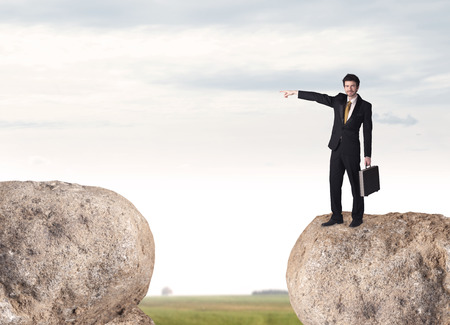 bridging the gap: Young businessman standing on edge of rock mountain