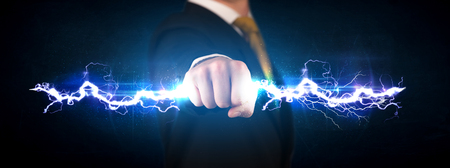 lightning bolt: Business man holding electricity light bolt in his hands concept