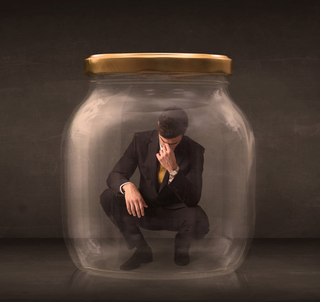 young fear: Businessman shut into a glass jar concept on background Stock Photo