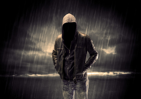 hackers: A faceless thief in unrecognizable hoodie standing in the middle of the night in the rain in front of landscape concept