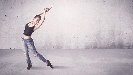women hips: A beautiful young hip hop dancer dancing contemporary urban street dance in empty clear grey wall background concept.