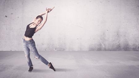 tänzerin: Eine schöne junge Hip-Hop Tänzer tanzen zeitgenössische urbane Streetdance in leeren klaren grauen Wand Hintergrund Konzept.