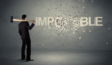 man power: Business man hitting impossible sign with hammer on grungy wall