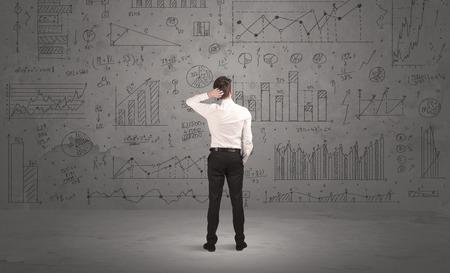 Ein erfolgreicher Geschäftsmann zuversichtlich, über Entscheidungen zu denken, vor der Wand stehen voll mit Grafik Tortendiagramme und Berechnungen Konzept