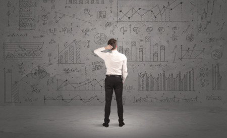 confundido: Un hombre de negocios confía en el éxito de pensar en las decisiones, de pie delante de la pared completa con gráficos de sectores gráfico y cálculos concepto