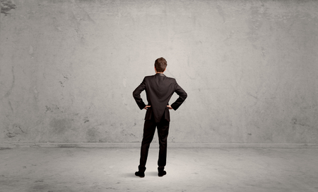A confused sales person having a dilemma, standing with his back in empty grey urban environment concept Stockfoto