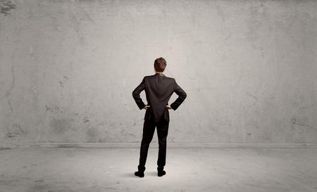confundido: Un vendedor que tiene un dilema confusa, de pie con la espalda en el concepto de medio ambiente urbano gris vacía Foto de archivo