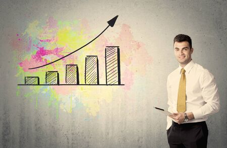 exponential: An elegant businessman standing in front of a grey wall with colorful growing chart drawing concept